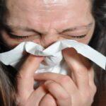 Kvinde der pudser næse i kleenex