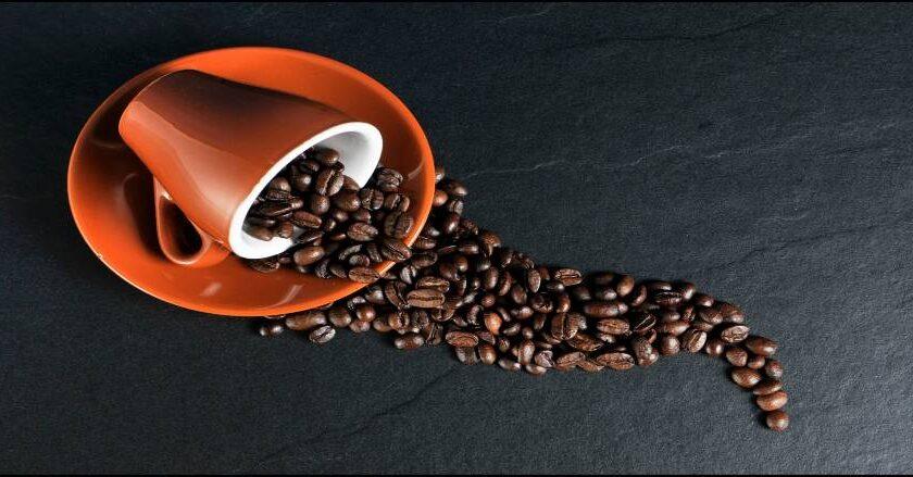 Kop med kaffebønner på bord